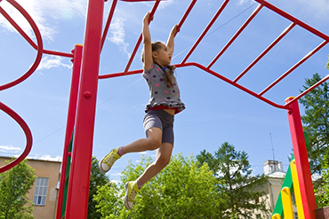 girl climbing on monkey bars